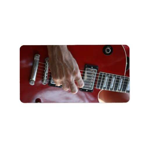 Hand playing red electric guitar near pickup custom address label
