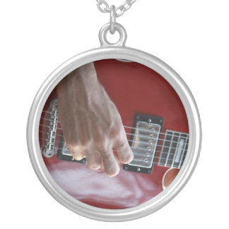 Hand playing red electric guitar near pickup pendants