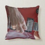Hand playing red electric guitar near pickup pillows