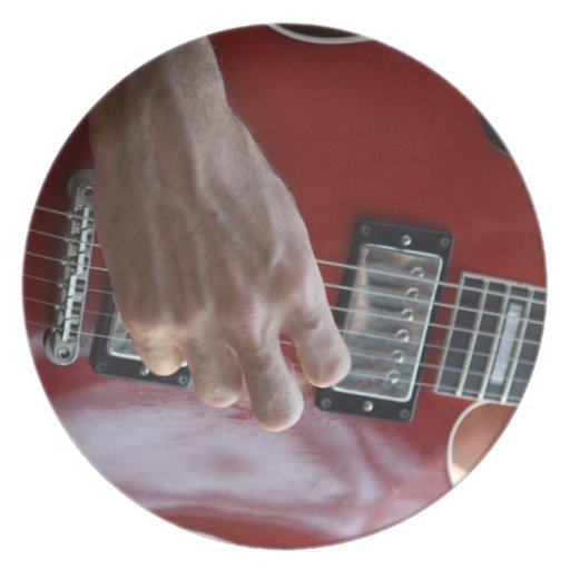 Hand playing red electric guitar near pickup dinner plates