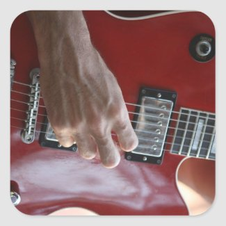 Hand playing red electric guitar near pickup sticker