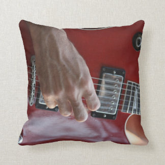 Hand playing red electric guitar near pickup throw pillow