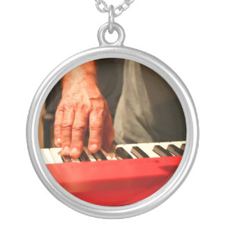 hand playing red keyboard male musician silver plated necklace