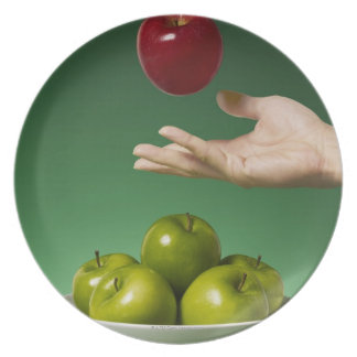 hand tossing red apple in the air and green dinner plate