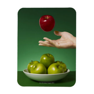 hand tossing red apple in the air and green rectangle magnet