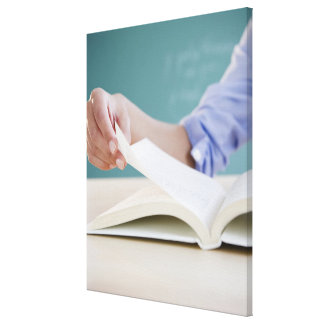 Hand turning page in book canvas print