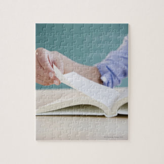 Hand turning page in book jigsaw puzzle