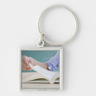 Hand turning page in book keychain