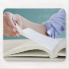 Hand turning page in book mouse pad