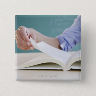 Hand turning page in book pinback button