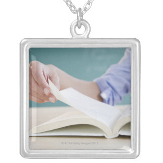 Hand turning page in book silver plated necklace