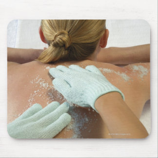 Hands applying exfoliating scrub mouse pad