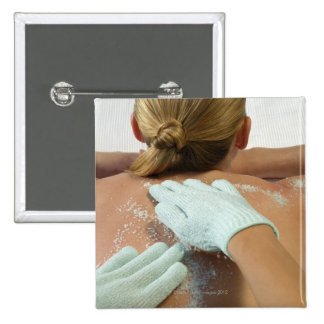 Hands applying exfoliating scrub pinback button