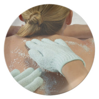 Hands applying exfoliating scrub party plates