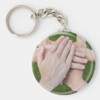 Hands arms uniting in glass sphere keychain