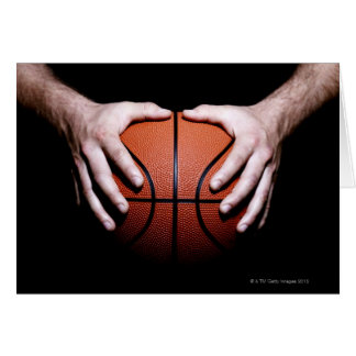 Hands holding a basketball card