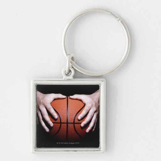 Hands holding a basketball keychains