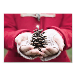 Hands holding a pine cone with a silver star card