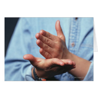 Hands making gesture: one hand held straight on card