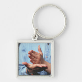 Hands making gesture: one hand held straight on keychain