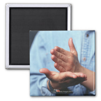 Hands making gesture: one hand held straight on magnet
