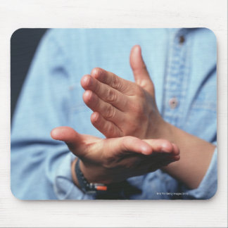 Hands making gesture: one hand held straight on mouse pad