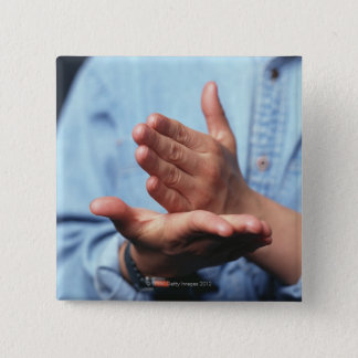 Hands making gesture: one hand held straight on pinback button
