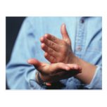 Hands making gesture: one hand held straight on postcard