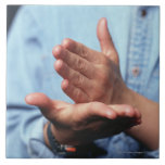 Hands making gesture: one hand held straight on tiles