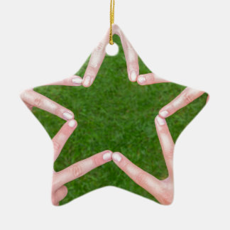 Hands of girls making star shape above grass ceramic ornament