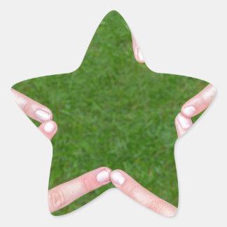 Hands of girls making star shape above grass star sticker