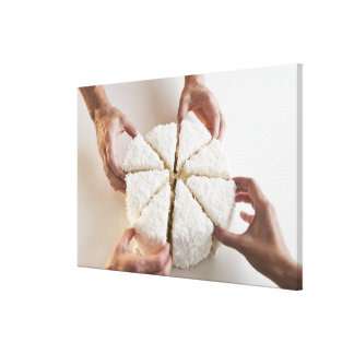 Hands pulling slices from cake canvas print
