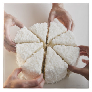 Hands pulling slices from cake ceramic tile