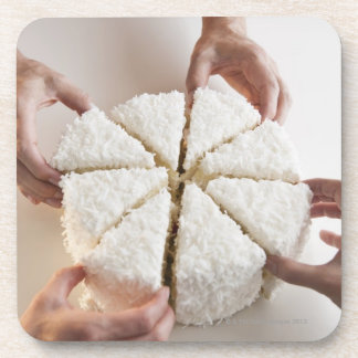 Hands pulling slices from cake drink coaster