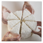 Hands pulling slices from cake large square tile