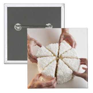 Hands pulling slices from cake pinback button
