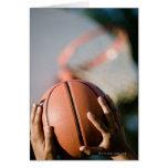 Hands shooting basketball outdoors card