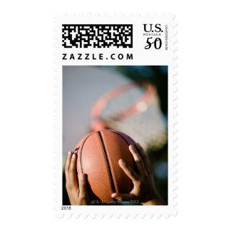 Hands shooting basketball outdoors postage