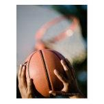 Hands shooting basketball outdoors postcard