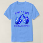 """Hanukkah Dreidels In Blue Cute Dreidel Champion T-Shirt<br><div class=""""desc"""">Add a name to this funny Dreidel Champion Hanukkah tee shirt for a personalized gift or as a little treat for yourself. The bold graphic design of the two Dreidels in bright shades of blue and white includes a template for your name above with """"Dreidel Champion"""" below, which can also...</div>"""