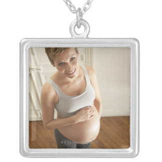 Happy pregnant woman standing on scale necklaces