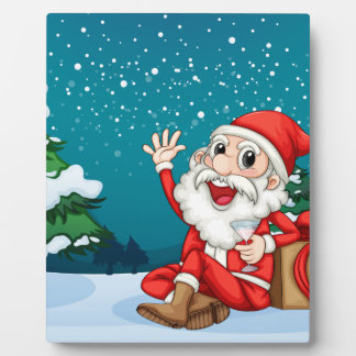 Happy Santa sitting in front of the pine tree Plaque