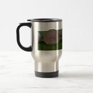 Hay bale rolls in a green field travel mug