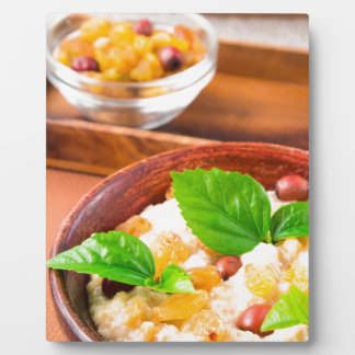 Healthy oatmeal with berries, raisins and herbs plaque