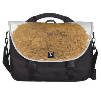 Heap of cinnamon powder on white background computer bag
