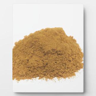Heap of cinnamon powder on white background plaque