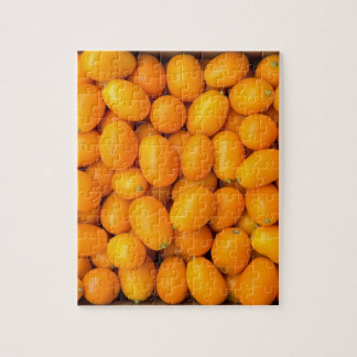 Heap of orange kumquats in cardboard box jigsaw puzzle