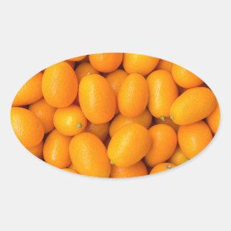 Heap of orange kumquats in cardboard box oval sticker