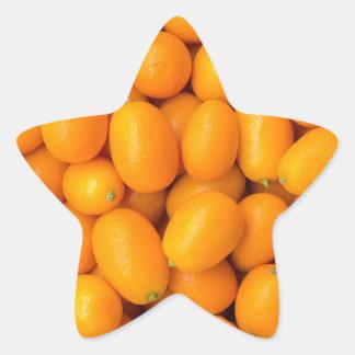 Heap of orange kumquats in cardboard box star sticker