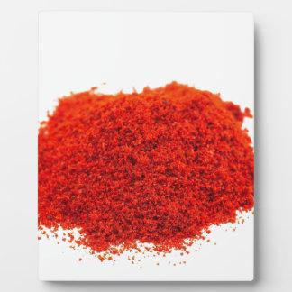 Heap of paprika powder on white background plaque